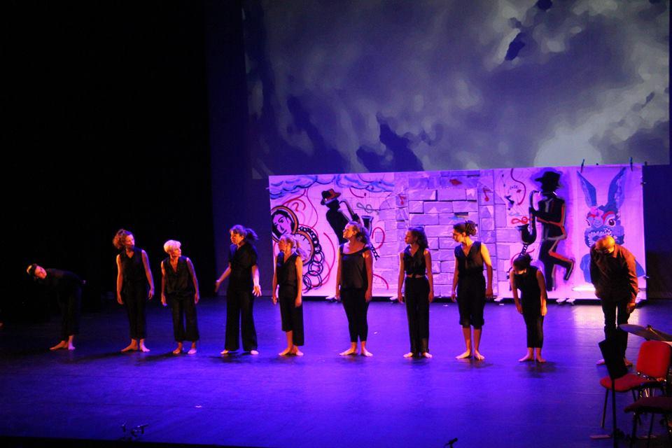 Ligne de danseuses devant un mur