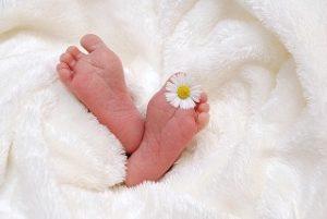 Les 2 pieds d'un bébé sortant de la couette