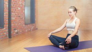 Une pratiquante de Yoga sur son tapisant