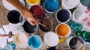 Une main tenant un pinceau prête à choisir sa couleur devant une multitude de pots de couleurs