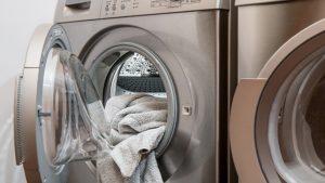 Un vêtement en cours de chargement dans une machine à laver