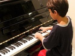 un enfant devant son clavier de piano